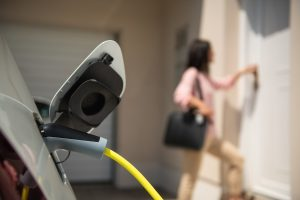 Close up of a electric car charger with female silhouette in the background, entering the home door